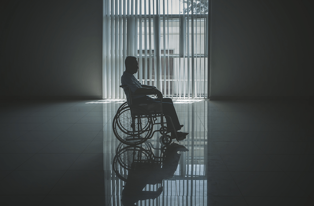 Photo of a man in wheelchair left alone in empty room