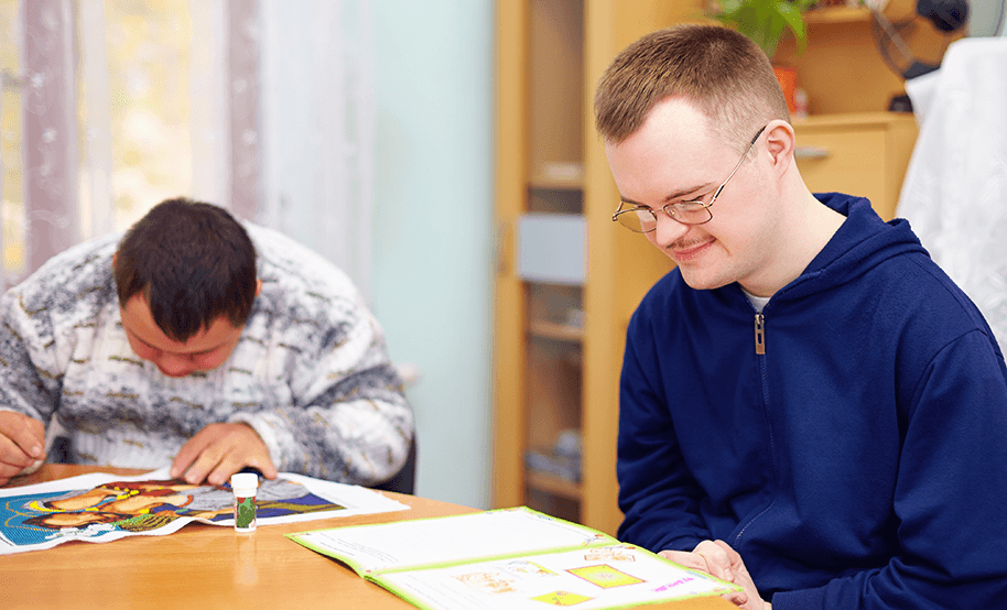 Photo of a man with intellectual impairment at table in group home