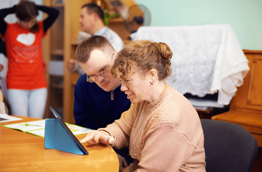 Photo of people with disability watching something on a tablet