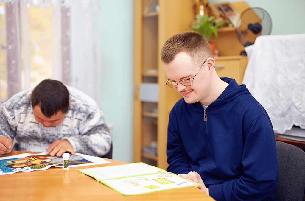 Photo of two men with disabilities in group home doing activities at a table.