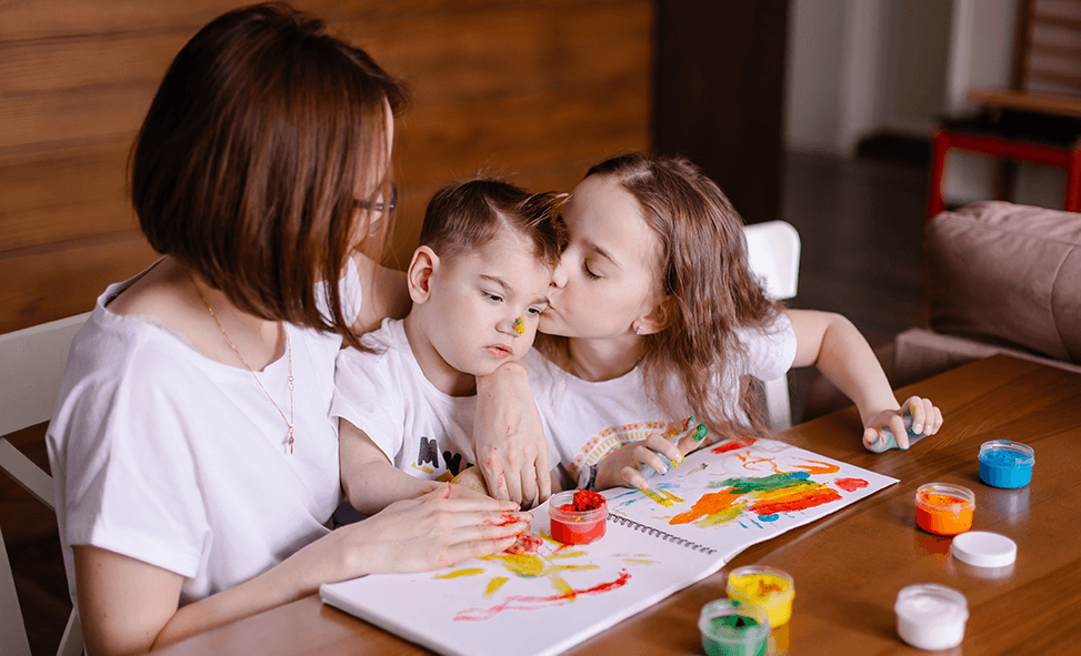 Photo of young boy with Cerebral Palsy finger painting with sister and mother