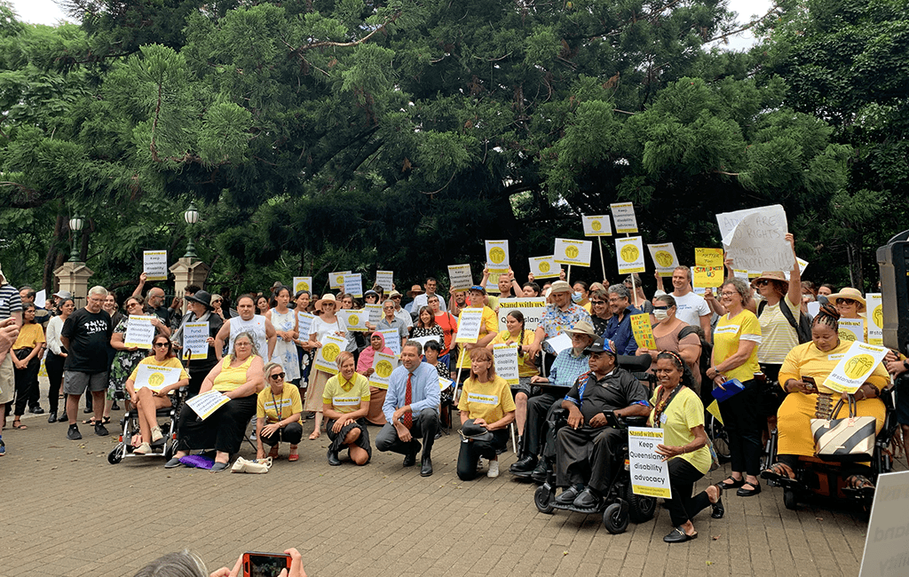 Photo of about 200 people in yellow holding placards, gathered together with the organisers and Minister Craig Crawford kneeling down in the front.