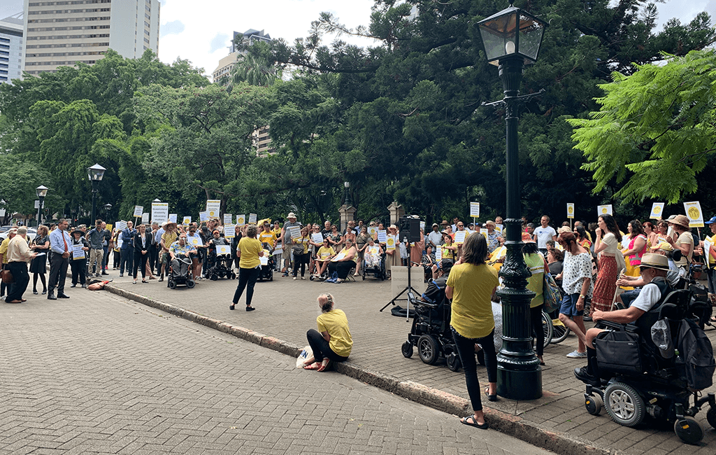Photo of about 200 people in yellow holding placards, standing in a large semi-circle listening to woman speaking in front of them.