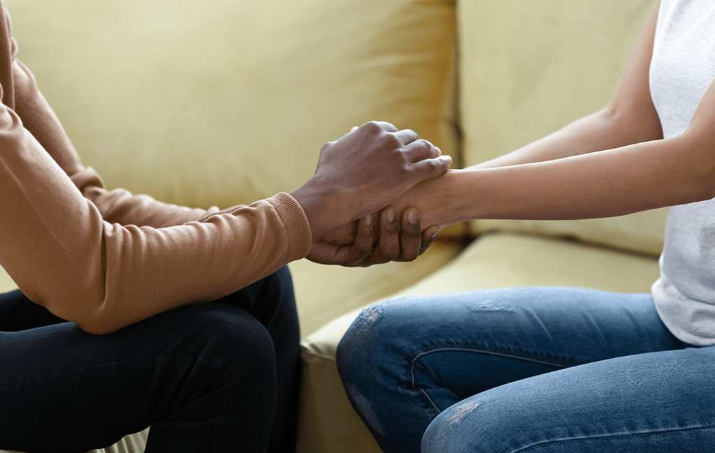 Photo of a black man holding hands with and comforting a black woman.