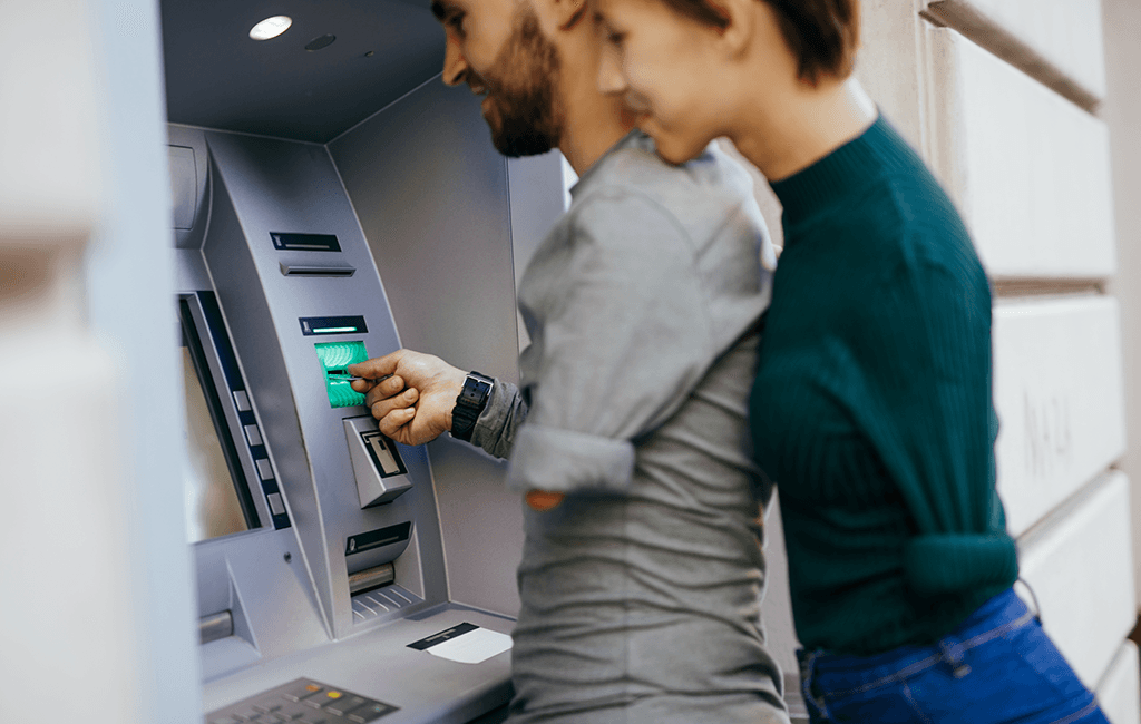 Photo of a couple who are each missing an arm, using an ATM